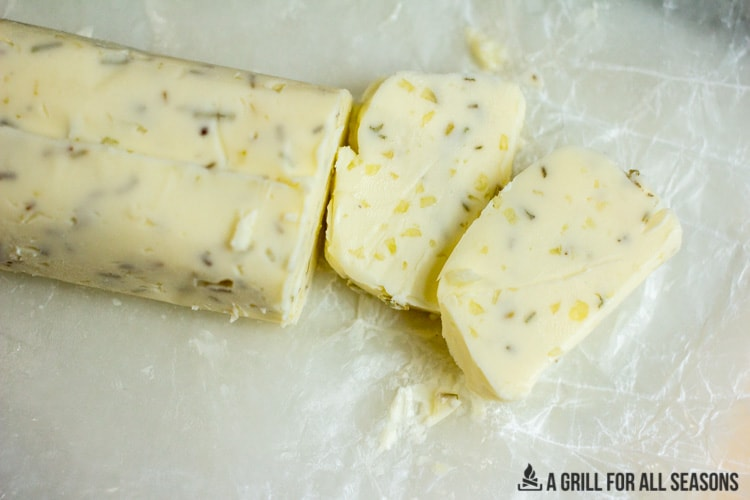Sliced garlic herb butter on a piece of waxed paper
