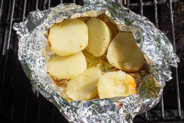 potato halves in foil on the grill