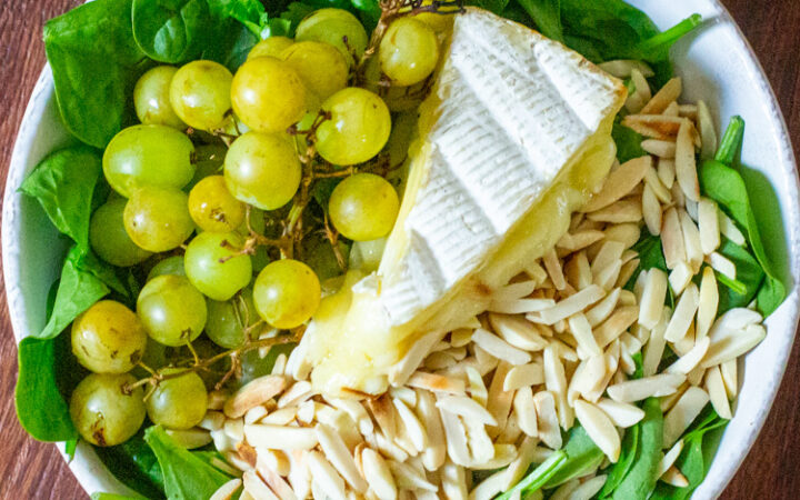 bowl with spinach grilled grapes brie cheese and slivered almonds