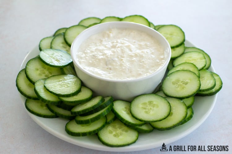 bowl of smoked onion dip on a platter with sliced cucumbers