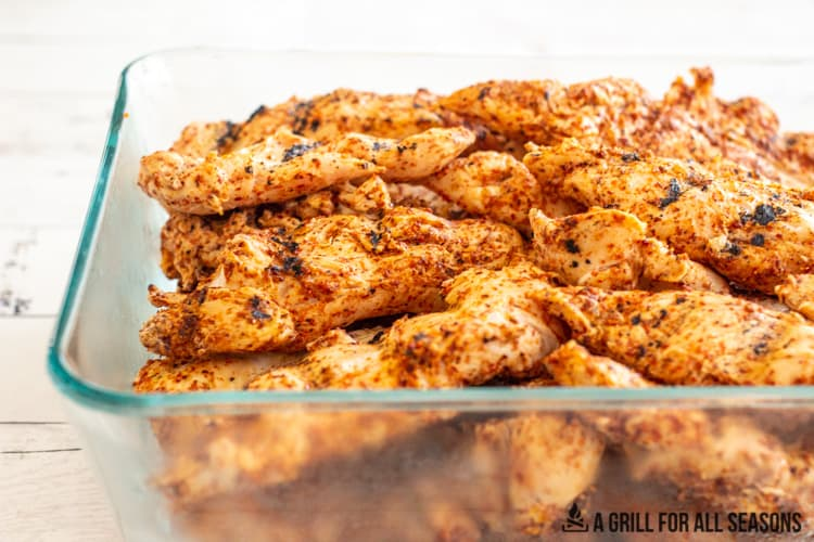 glass dish with tajin chicken tenderloins that have been grilled