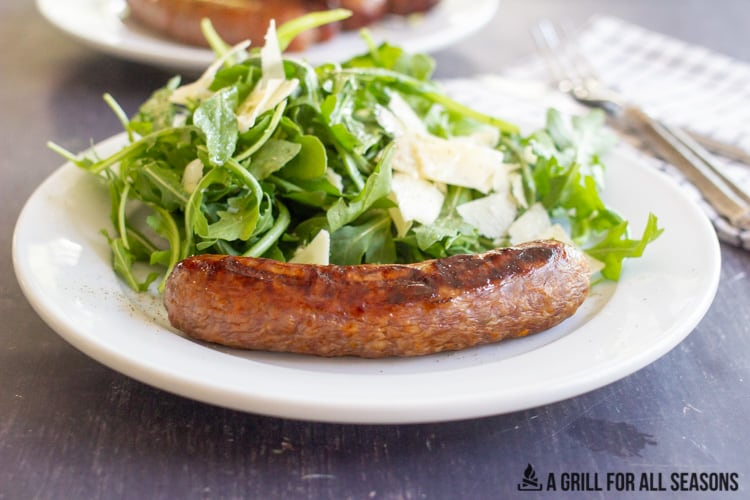 Italian sausage on a plate with a side salad