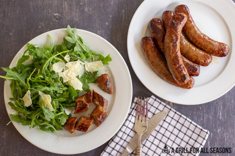 Air Fryer Sausages sliced on a plate with a salad