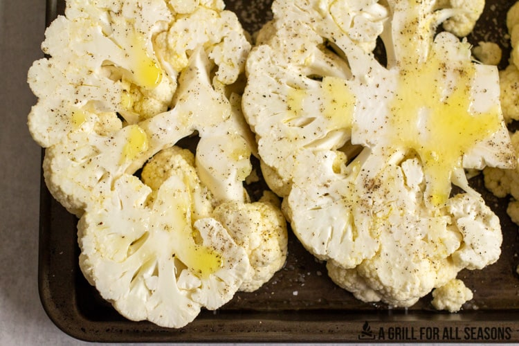 cooking sheet with sliced cauliflower seasoned with salt, pepper and olive oil.