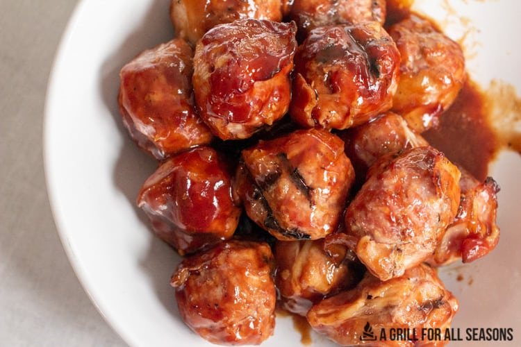 smoked meatballs with bacon on a white plate glazed with bbq sauce