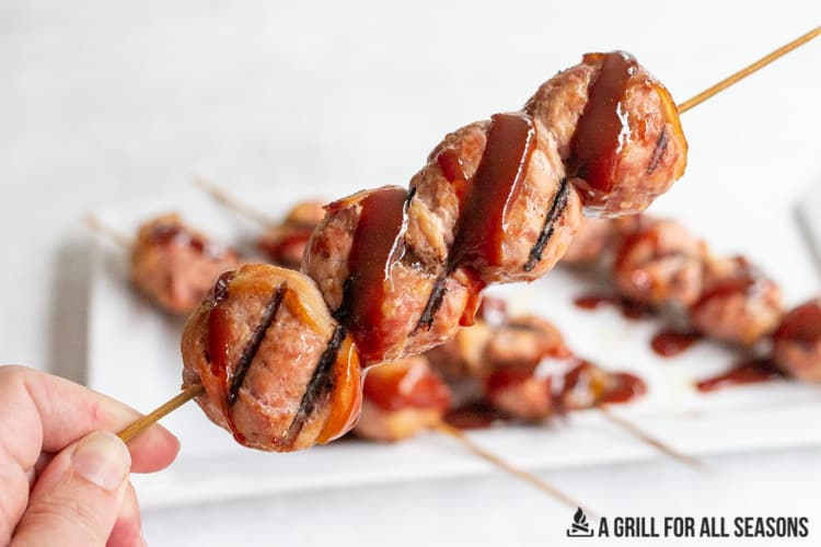 hand holding a skewer of cooked smoked meatballs covered in bbq sauce