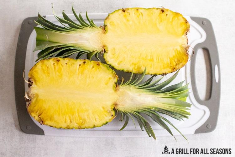 pineapple cut in half on a cutting board
