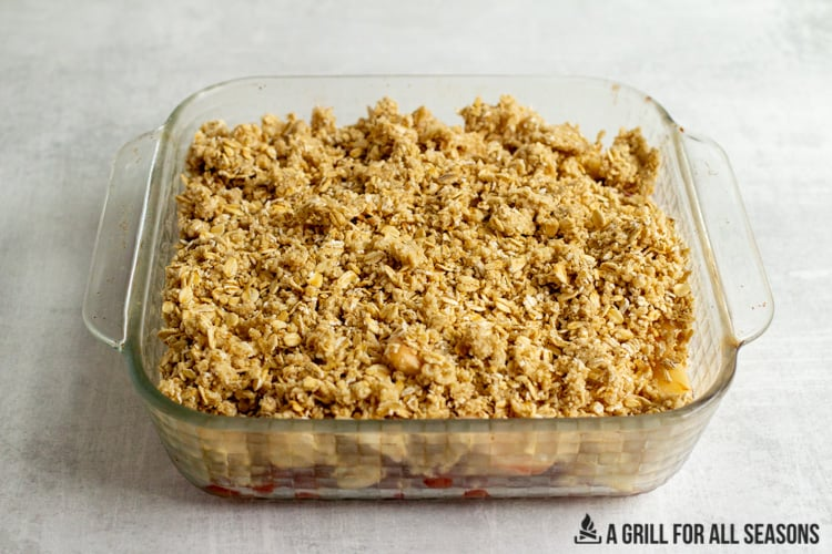 oatmeal topping on a fruit crisp in an 8x8 glass pan