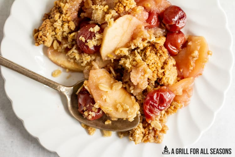 small plate with a serving of Apple and Cherry Crumble and a spoon