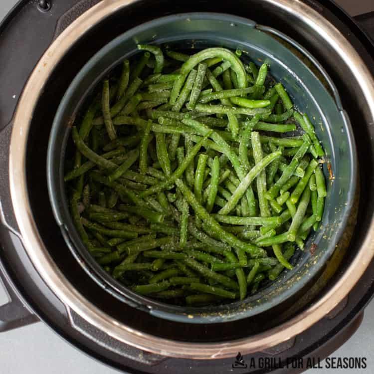air fryer basket with vegetables in it