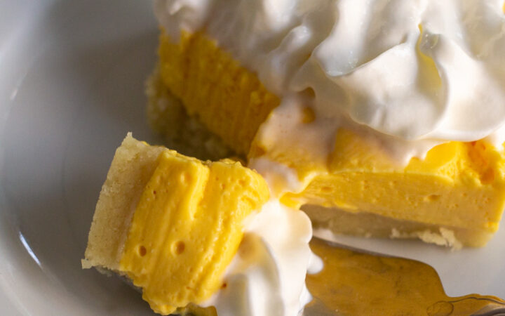 one of the No Bake Mango Cheesecake Bars on a plate with a bite on a fork
