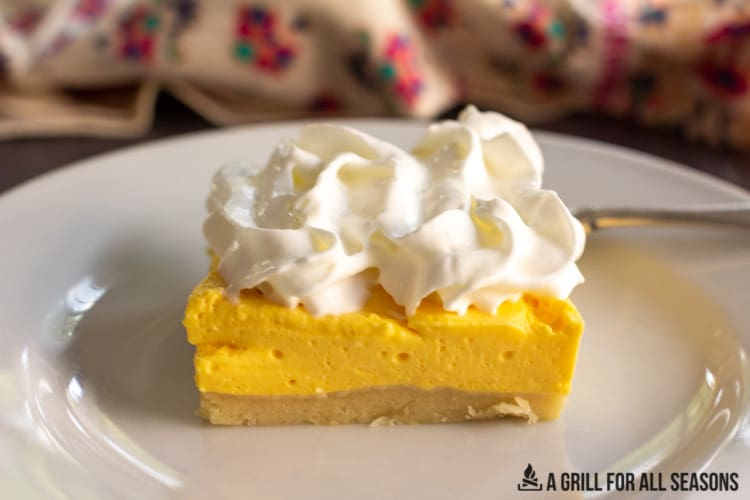 one of the No Bake Mango Cheesecake Bars on a plate topped with whipped cream