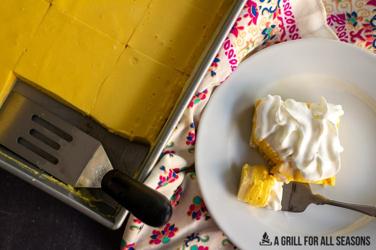 one of the No Bake Mango Cheesecake Bars on a plate with the rest in the pan next to it