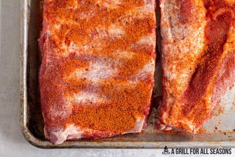 raw pork spareribs on tray with a rub