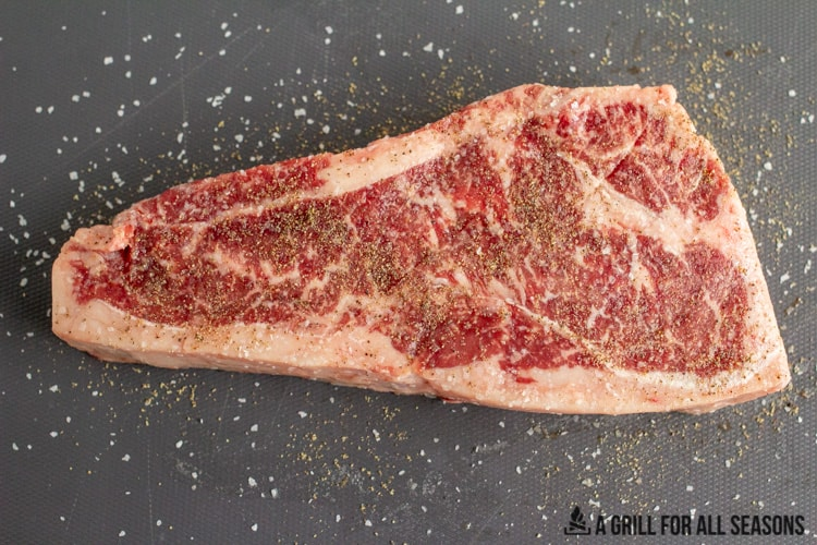 raw steak on cutting board seasoned with salt and pepper