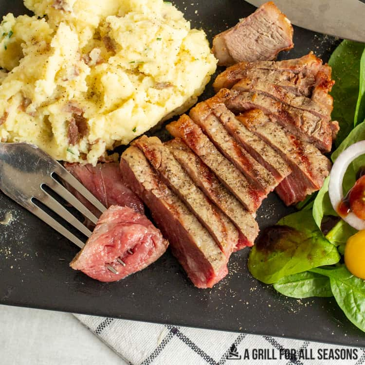 plate with sliced steak, mashed potatoes and a side salad.