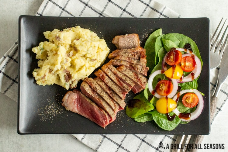 plate with sliced pellet grill steak, mashed potatoes and a side salad.