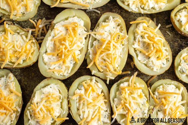 potatoes with filling and topped with shredded cheese