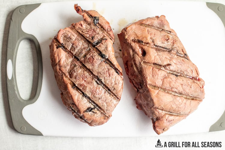 two sirloins on a cutting board with grilled lines