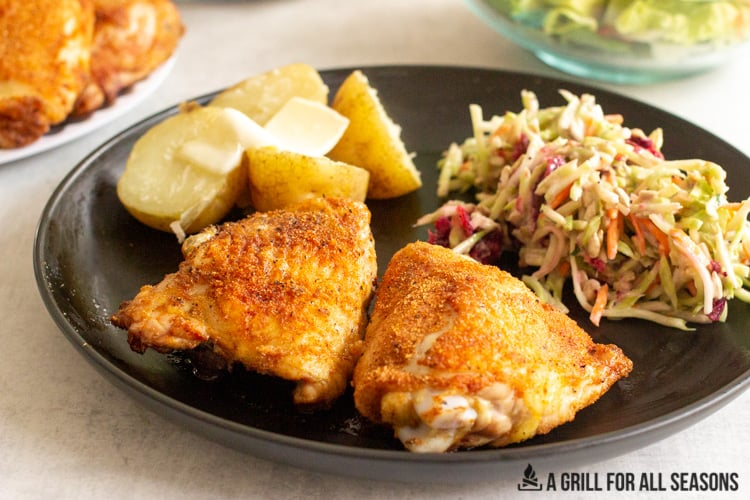 cooked Traeger Chicken Thighs on plate with potatoes and a slaw.