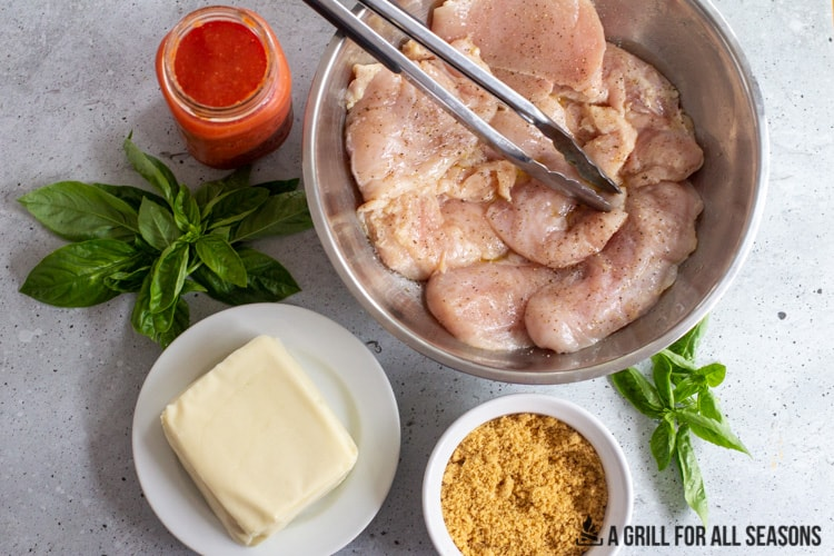 block of mozzarella cheese, jar of tomato sauce, basil leaves, ground pork rinds for breading and bowl of cutlets seasoned with salt and pepper.