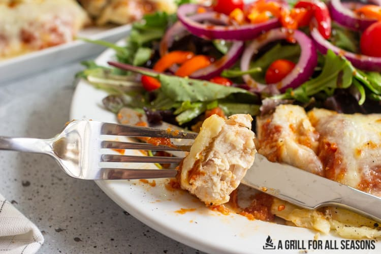 Plate with chicken parm and garden salad with fork holding piece of chicken parm.
