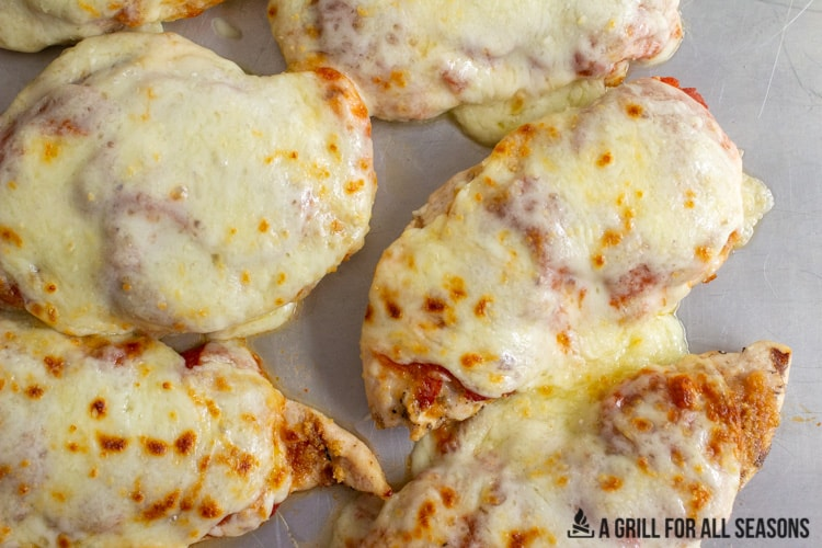 several pieces of grilled chicken parm on cooking tray