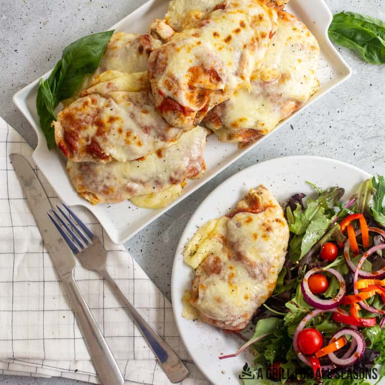 tray of grilled chicken parm and dish with piece of chicken parm accompanied by a garden salad.
