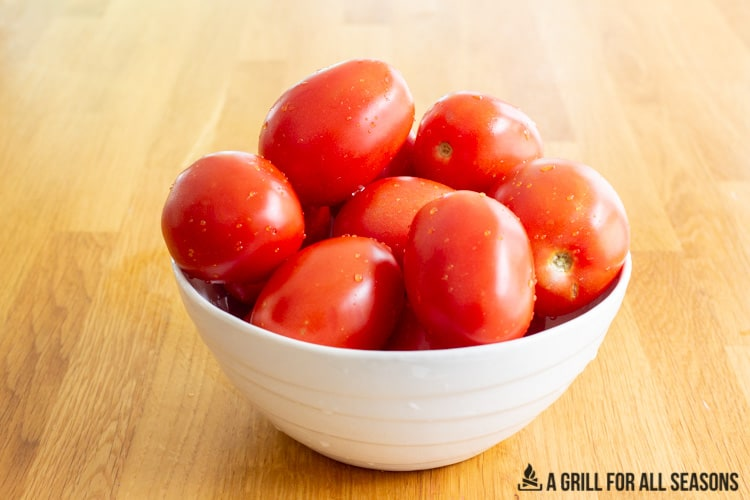 White bowl filled with plum tomatoes.