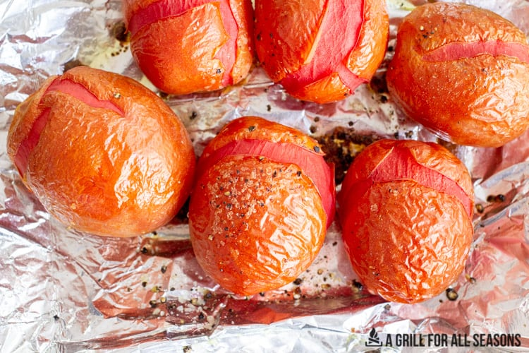 Smoked plum tomatoes with charred cracked skin on foil.
