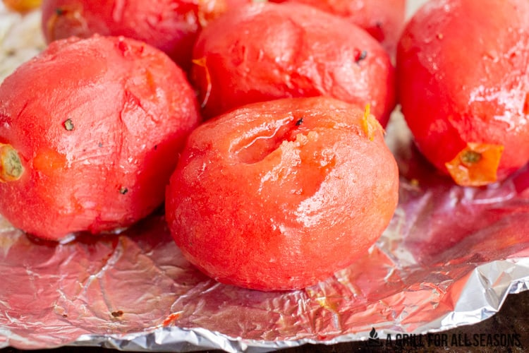 Smoked plum tomatoes with the skin removed on foil.