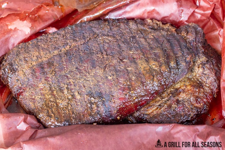 Whole smoked brisket resting unwrapped in butcher paper.