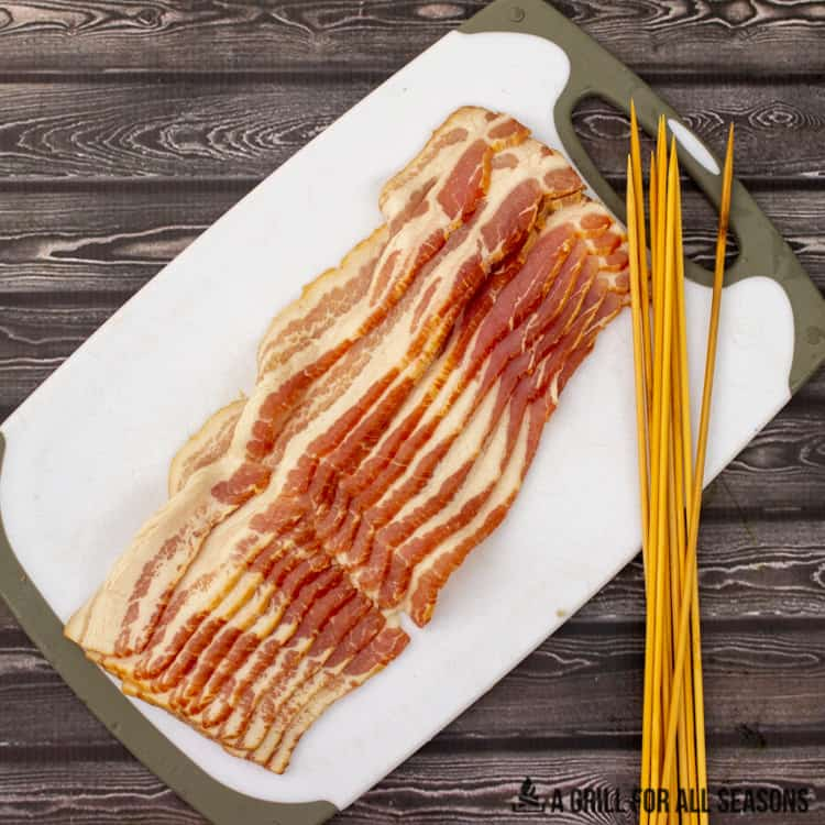 Raw slices of bacon on a cutting board next to bamboo skewers.