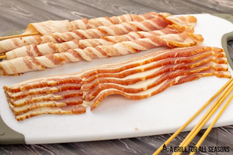 Process shot of raw bacon slices as well as some bacon wrapped around bamboo skewers sitting on a cutting board.