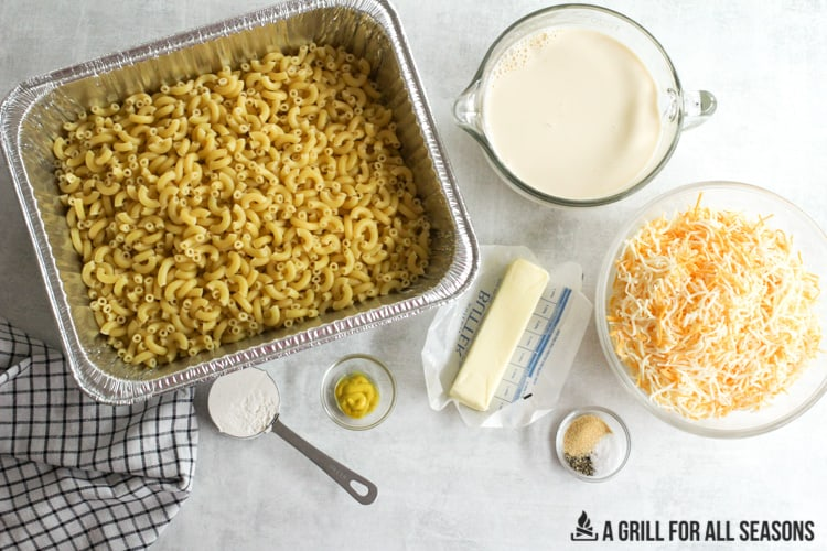 cooked elbow pasta in a tray with other ingredients in small bowls