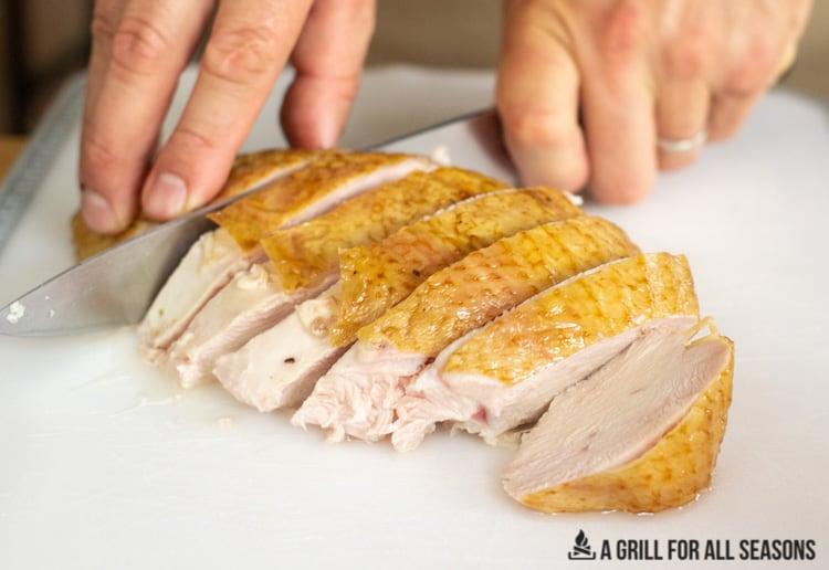 Slicing a smoked turkey breast on a cutting board.