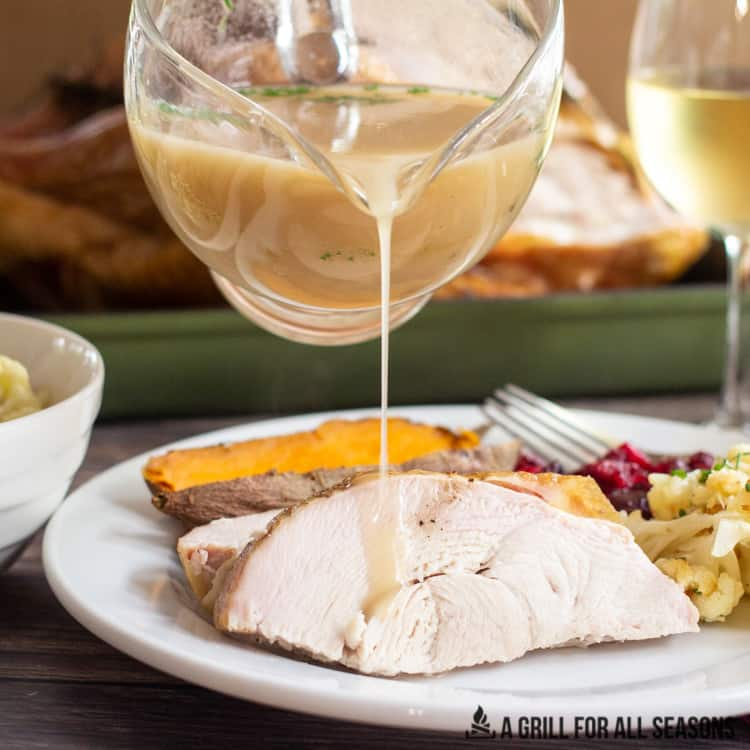 Gravy being poured over sliced turkey on a plate with cranberry sauce, sweet potatoes and roasted cauliflower.
