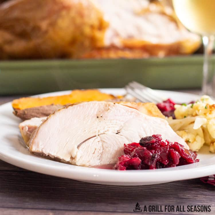 Sliced smoked turkey served on a plate with cranberry sauce, roast cauliflower and sweet potato.
