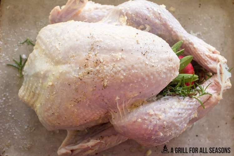 Whole turkey on cooking sheet stuffed with halved apples and fresh herbs, with outer skin rubbed with butter and salt and pepper.
