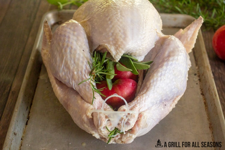 Whole turkey on cooking sheet stuffed with halved apples and fresh herbs.