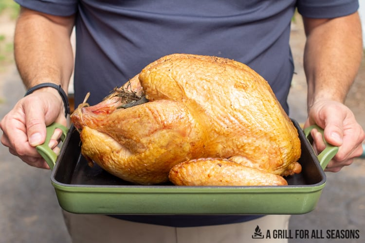Whole smoked turkey being held in roasting pan.