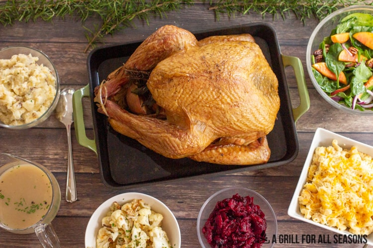 Whole smoked turkey in roasting pan surrounded by a variety of side dishes including mac and cheese, roasted cauliflower, salad, gravy, cranberry sauce and mashed potatoes.